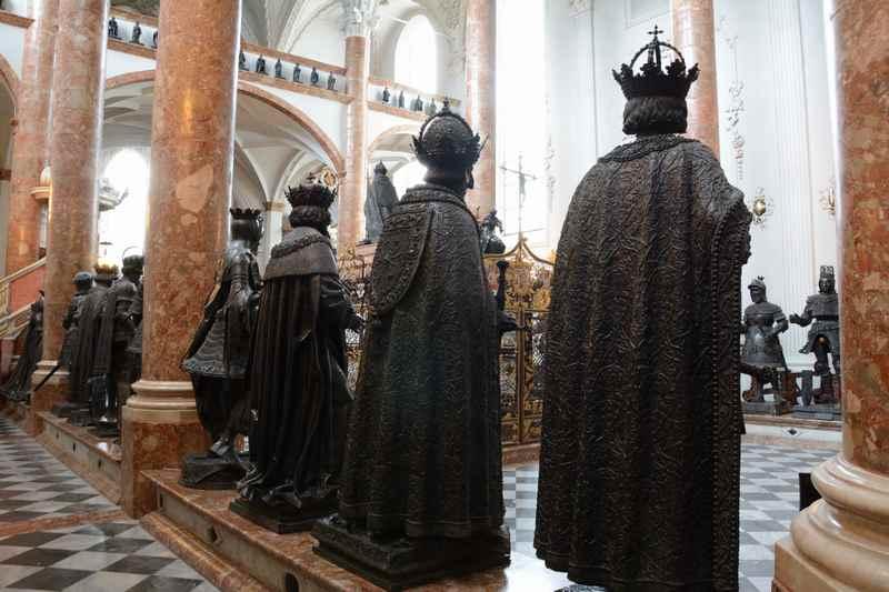 """Hofkirche Innsbruck: Rund um das Grabmal stehen die schwarzen Figuren des Adels, die """"schwarzen Mander"""""""